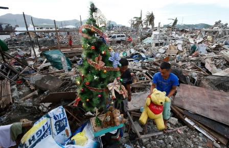 Typhoon survivor decorates Christmas tree amid trubble of destroyed houses in Tacloban